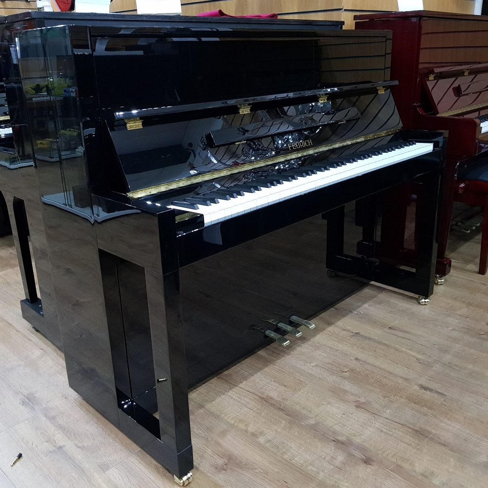 Feurich 115 Premiere upright piano, in a black polyester case.